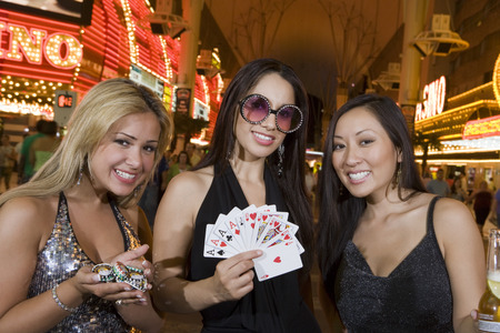 Portrait of three young women with playing cards and gambling chips in front of casino, Las Vegas, Nevada, USA