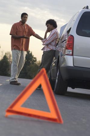 壊れた車、背景の人々 の前に三角形の警告