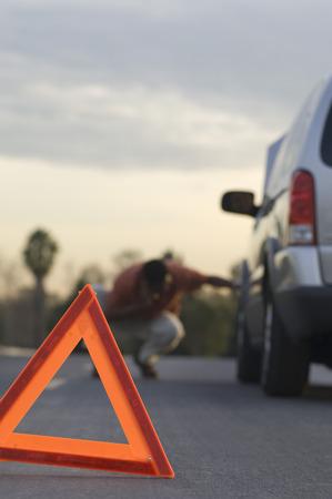 前の警告三角形分割車、背景の男