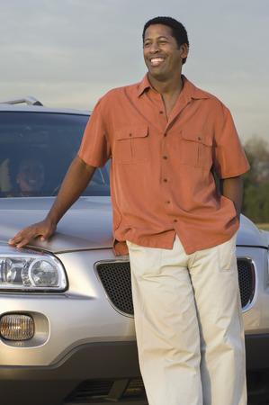 成人男性の車の前に半ば笑みを浮かべて