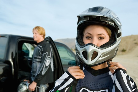 role reversal: Motocross Racer Putting on Helmet