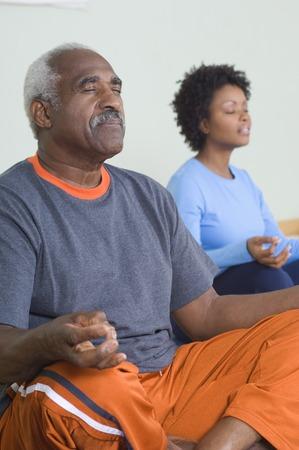 65 70 years: Senior Man Meditating in Yoga Class LANG_EVOIMAGES