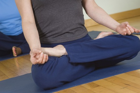 cropped off: Woman in Lotus Posture in Yoga Class