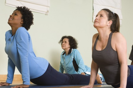 racially diverse: Women Stretching Backs in Yoga Class