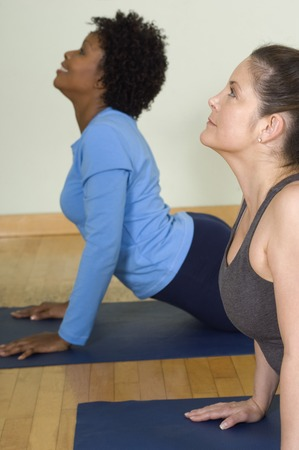 40 year old woman: Women Stretching Backs in Yoga Class