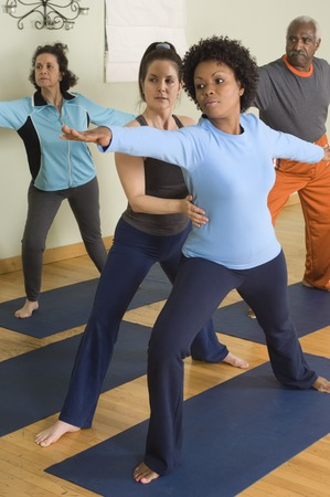 racially diverse: Yoga Instructor Assisting Woman in Yoga Class