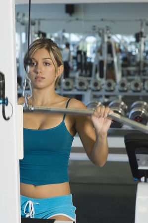 weight machine: Young Woman Working Out on Weightlifting Machine