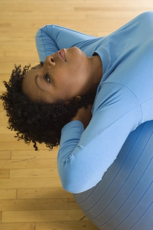 well beings: Woman Doing Sit-Ups With Exercise Ball LANG_EVOIMAGES