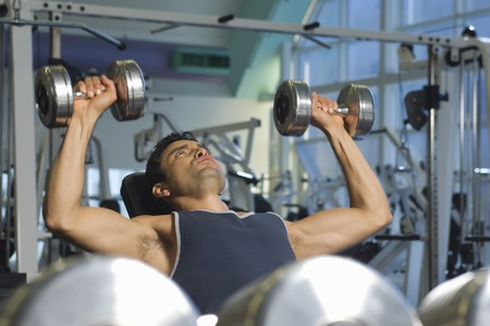 muscle toning: Man Weightlifting on Bench With Dumbbells