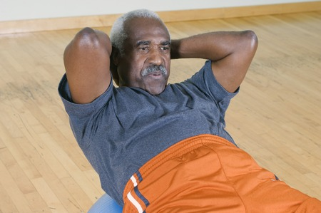 Senior Man Doing Sit-Ups on Exercise Ball Stock Photo - 5478266