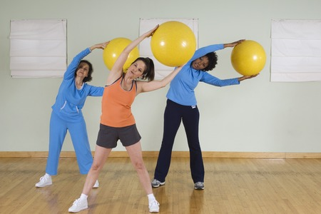 racially diverse: Women Using Exercise Balls in Fitness Class LANG_EVOIMAGES