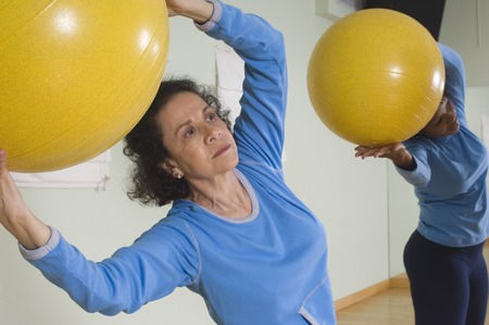 70s adult: Senior Woman Using Exercise Ball in Fitness Class