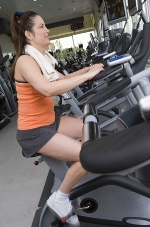 Woman Working Out on Exercise Bicycle in Gym Stock Photo - 5478274