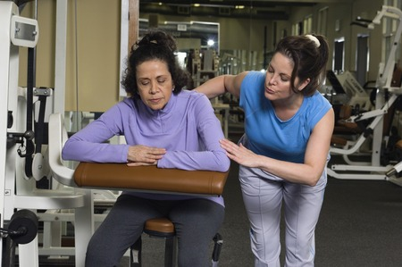 Trainer Assisting Senior Woman on Exercise Machine Stock Photo - 5478288