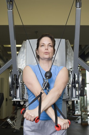 muscle toning: Woman Working Out on Weightlifting Machine LANG_EVOIMAGES