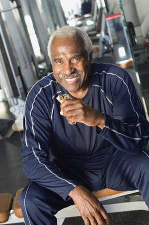 70s adult: Senior Man Eating Healthy Snack at Gym