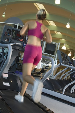 cardiovascular exercising: Woman Jogging on Treadmill at Gym LANG_EVOIMAGES