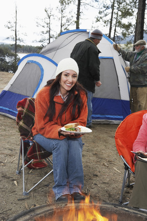 Woman Eating Sandwich by Campfire Stock Photo - 5478312