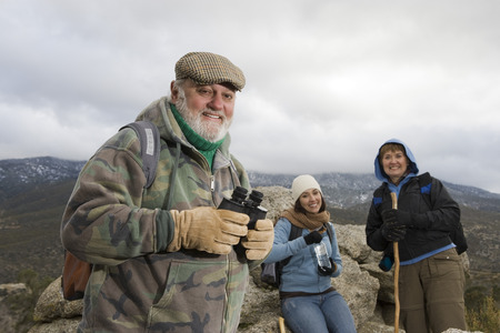 Senior man holding binoculars in mountains Stock Photo - 5478360