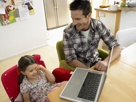 Father and Daughter Using Laptop at Kitchen Table