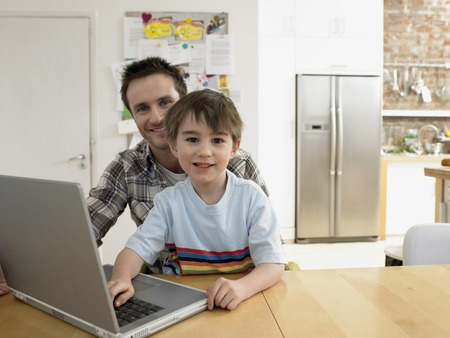 late 30s: Smiling Father and Son Using Laptop in Kitchen