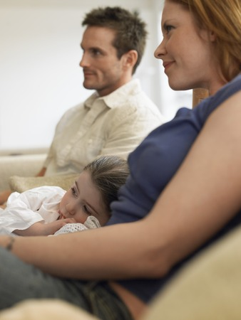 early thirties: Family Watching TV on Couch