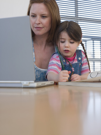 late 30s: Mother Using Laptop While Daughter Colors