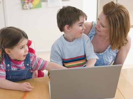 late 30s: Mother and Children at Table With Laptop