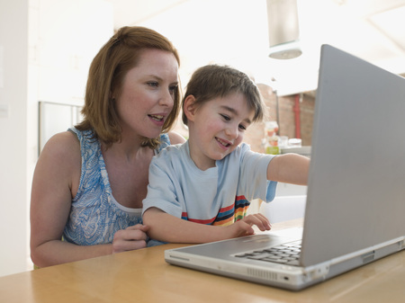 helpfulness: Mother Helping Son Use Laptop LANG_EVOIMAGES