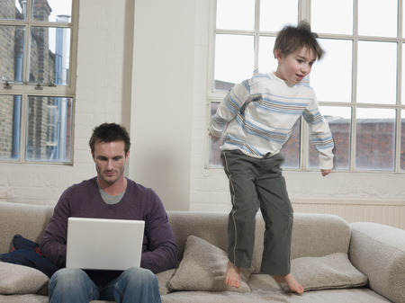 misbehaving: Father Using Laptop as Son Jumps on Sofa