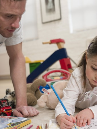 35 years old man: Girl on Floor Coloring With Father