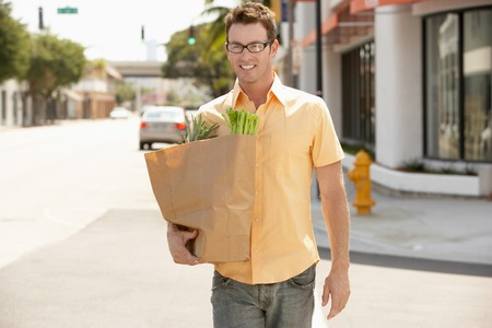 after shopping: Man Carrying Groceries Home After Shopping