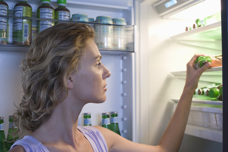 Young woman looking for food in fridge Stock Photo - 5478646