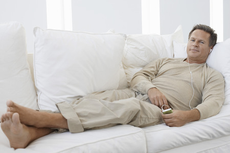 one mature man only: Man Listening to iPod on Sofa