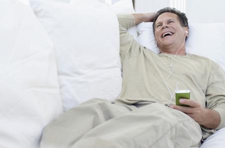enjoyable: Man Listening to iPod on Sofa