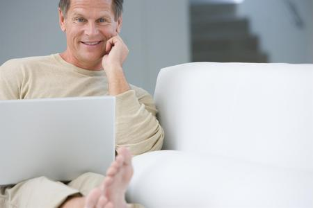 Middle-aged man with laptop on sofa Stock Photo - 5478669