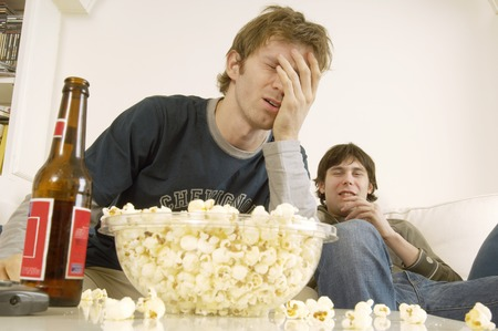 early twenties: Upset Young Man on Sofa with Popcorn and Beer