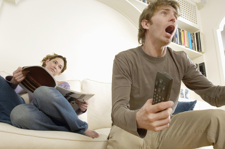 fervour: Young Woman Reading Magazine next to Boyfriend Cheering at Television LANG_EVOIMAGES