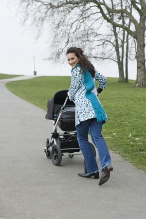 empujando: Mother pushing stroller in park LANG_EVOIMAGES