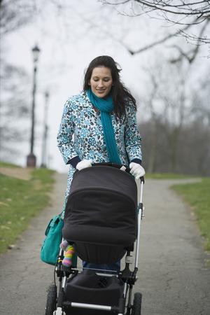 one parent: Mother pushing stroller in park LANG_EVOIMAGES