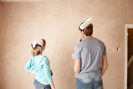 early thirties: Couple Preparing to Paint Room Together
