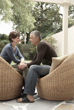 seating furniture: Couple Sitting in Wicker Chairs on Patio