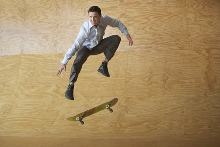 halfpipe: Young Businessman Performing Skate Trick in Half-Pipe