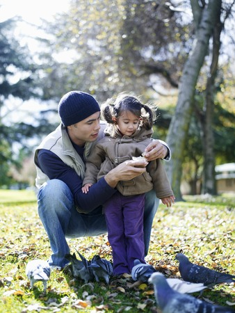 en cuclillas: Padre e hija comer a las palomas LANG_EVOIMAGES