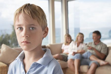Boy Standing in Zimmer mit Familie im Hintergrund