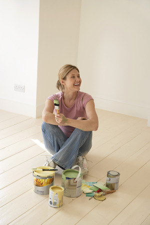 no kw 1: Smiling Woman Sitting with Painting Supplies on Floor LANG_EVOIMAGES