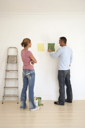 Woman Watching Boyfriend Test Paint Colors on Wall LANG_EVOIMAGES