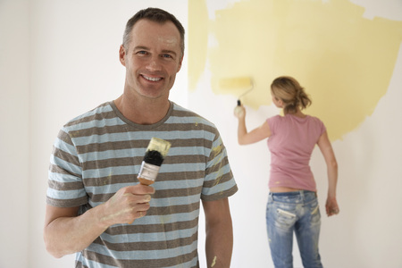 Smiling Man Holding Paintbrush while Girlfriend Paints Wall with Roller