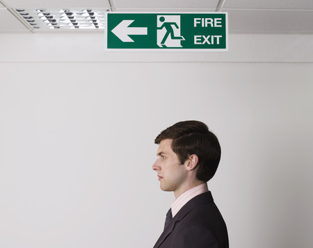 fantasize: Young Businessman Standing Under Exit Sign LANG_EVOIMAGES