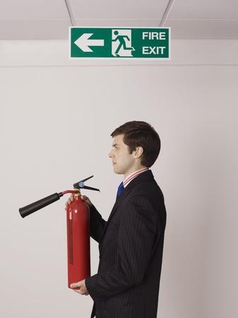 under fire: Businessman Holding Fire Extinguisher Under Exit Sign LANG_EVOIMAGES